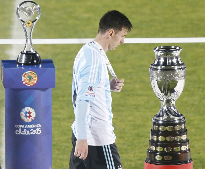 http://im.rediff.com/sports/2015/jul/05argentina1.jpg Argentina's Lionel Messi walks with his silver medal past the Copa America trophy