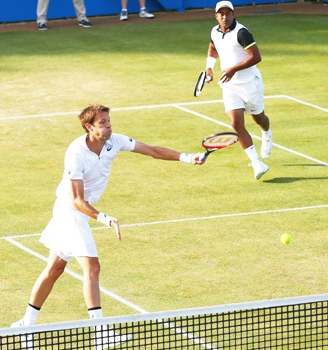 Canada's Daniel Nestor of Canada smashes as his partner Leander Paes