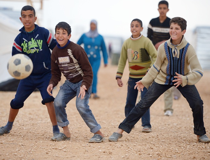 Boys play football as Syrian refugees go about their daily business