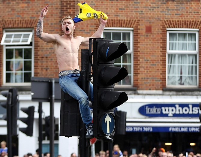 A Chelsea fan climbs on a set of traffic lights