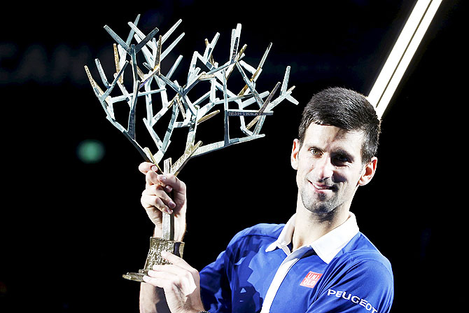 World number one Novak Djokovic of Serbia poses with the trophy after beating Britain's Andy Murray in their Paris Masters final on Sunday