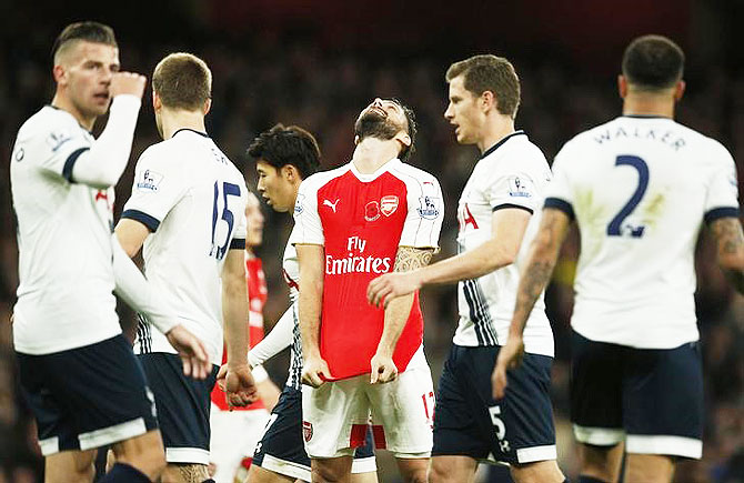 Arsenal's Olivier Giroud looks dejected after missing a chance to score a Tottenham players look on