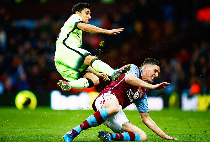 Manchester City's Jesus Navas is tackled by Aston Villa's Ciaran Clark during the Barclays Premier League match at Villa Park in Birmingham on Sunday