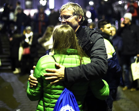 People comfort each other shortly after the match between Germany and the Netherlands was cancelled following a bomb alert at the HDI-Arena in Hanover on Tuesday