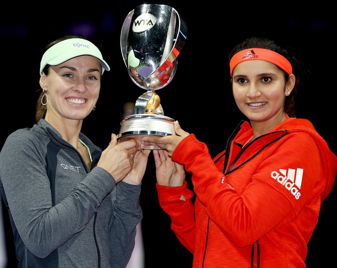 India's Sania Mirza, right, and Switzerland's Martina Hingis hold up the Martina Navratilova Doubles Trophy