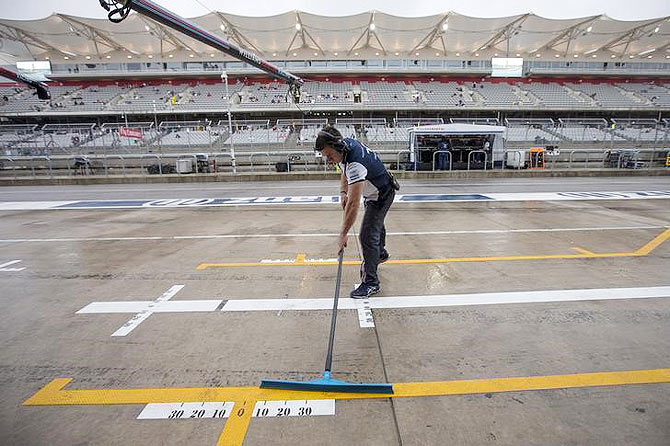 A Williams Formula One pit crew member clears rain water from pit lane ahead of the first practice session of the US F1 Grand Prix at the Circuit of The Americas in Austin, Texas on Friday