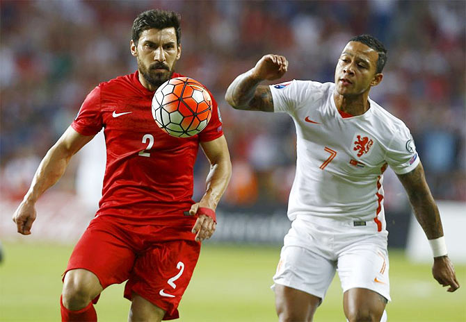 Turkey's Sener Ozbayrakli (L) fights for the ball with Memphis Depay of the Netherlands