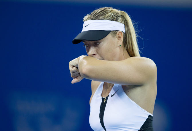 Russia's Maria Sharapova wipes her face as she plays against Czech Republic's Barbora Strycova during their women's singles match at the Wuhan Open tennis tournament, in Hubei province, China, on Monday