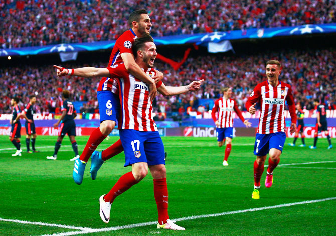 Atletico Madrid's Saul Niguez (17) celebrates with teammate Koke and others after scoring against Bayern Munich during the UEFA Champions League semi-final first leg match at Vincente Calderon Stadium in Madrid