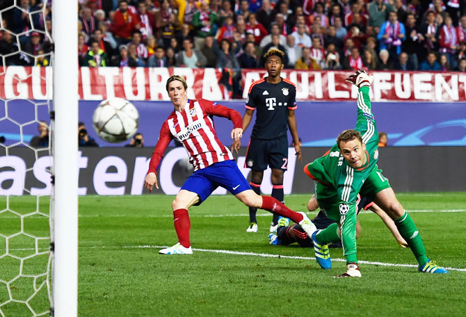 Atletico Madrid's Fernando Torres watches as his effort beats Bayern Munich's 'keeper Manuel Neuer, but only manages to hit the post