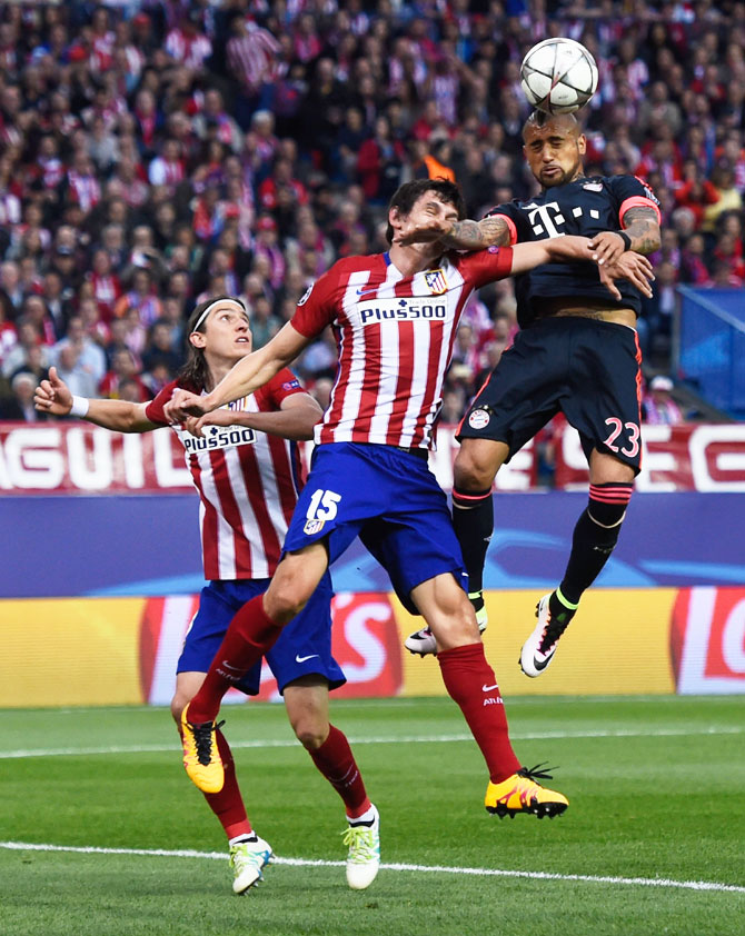 Bayern Munich's Arturo Vidal outjumps Atletico Madrid's Felipe Luis and Stefan Savic (15) to win a header