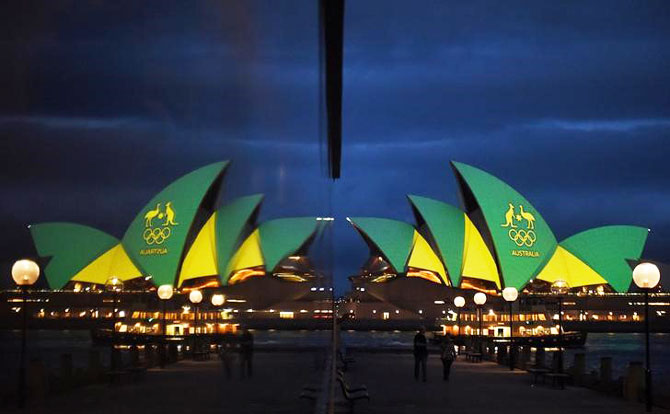 The Sydney Opera House is illuminated with the green and gold colours of the Australian Olympic team and reflected in a hotel window in Sydney, Australia, before the Olympics opening ceremony in Rio de Janeiro, Brazil, on Friday