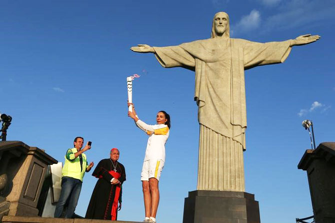 Former Brazilian volleyball player Isabel Barroso holds the Olympic torch next to Christ the Redeemer statue watched by Rio Mayor Eduardo Paes (L) and archbishop Orani Joao Tempesta in Rio de Janeiro on Friday