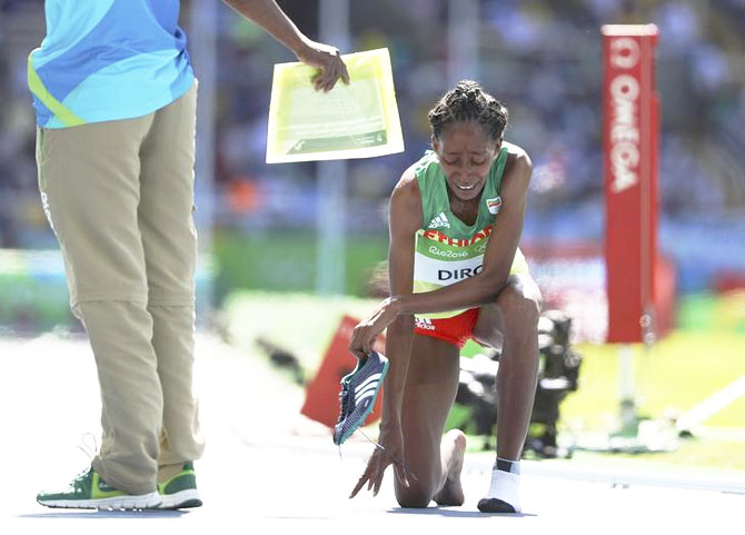 Ethiopia's Etenesh Diro reacts after she competed most of the 3000m Steeplechase race without one shoe