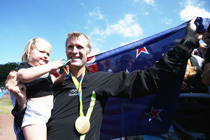 Gold medalist Mahe Drysdale of New Zealand celebrates with his daughter Bronte after the medal ceremony for the Men's Single Sculls on Saturday