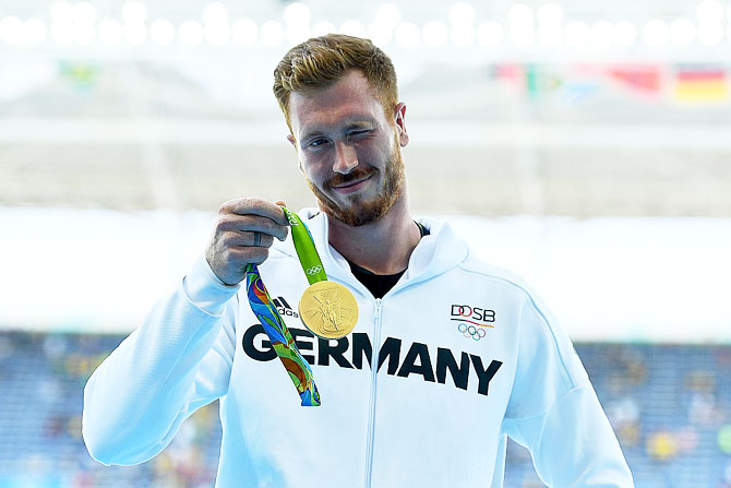 Gold medalist Christoph Harting of Germany poses on the podium during the medal ceremony for the Men's Discus Throw Final on Saturday