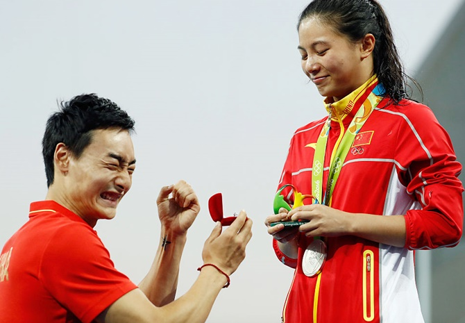 Chinese diver Qin Kai proposes to silver medalist He Zi of China on the podium during the medal ceremony for the Women's Diving 3m Springboard Final on August 14