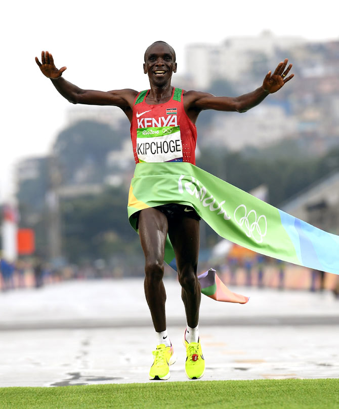 Kenya Eliud Kipchoge celebrates as he crosses the line to win gold in the men's marathon