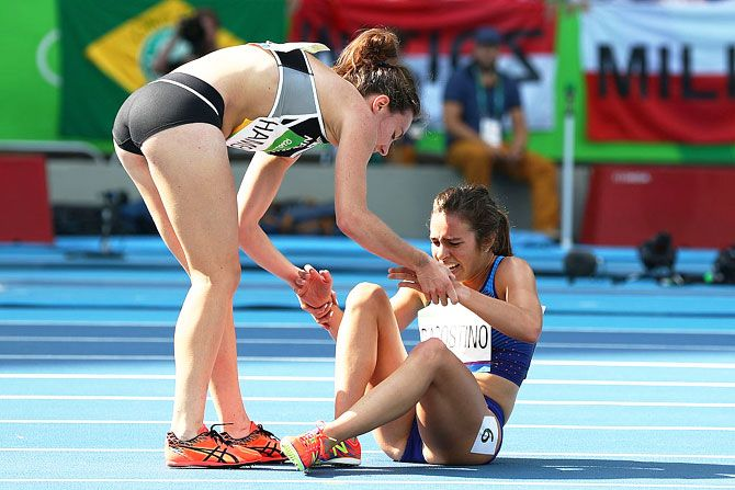 Abbey D'Agostino of the United States (right) is assisted by Nikki Hamblin of New Zealand after they collided during the Women's 5000m Round 1 - Heat 2 at the Olympic Stadium on August 16