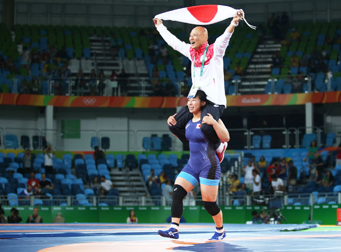 Sara Dosho of Japan celebrates with her coach after winning the gold medal in the Women's Freestyle 69 kg event on August 17