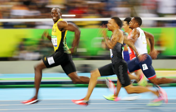 Usain Bolt of Jamaica looks at Andre De Grasse of Canada as they compete in the men's 100m semi-final at Olympic Stadium in Rio de Janeiro on August 14