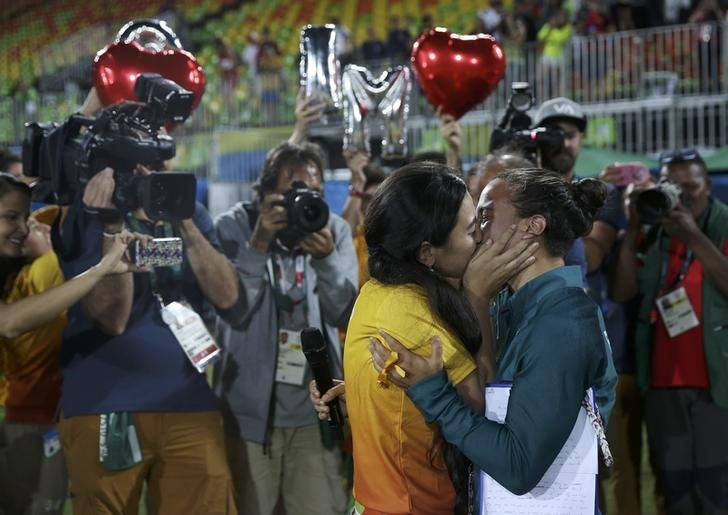 Rugby player Isadora Cerullo (BRA) of Brazil kisses Marjorie, a volunteer, after receiving her wedding proposal on the sidelines of the women's rugby medal ceremony