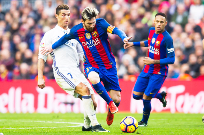 FC Barcelona's Lionel Messi wins the ball past Real Madrid's Cristiano Ronaldo as Neymar (in background) watches, during their El Clasico La Liga match at Camp Nou, last December
