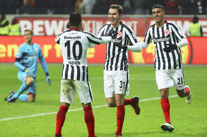 Eintracht Frankfurt's Branimir Hrgota (centre) celebrates his goal against FSV Mainz 05 with Marco Fabian (left) and Ayman Barkok during their match against Mainz 05 at Commerzbank Arena, in Frankfurt on Tuesday