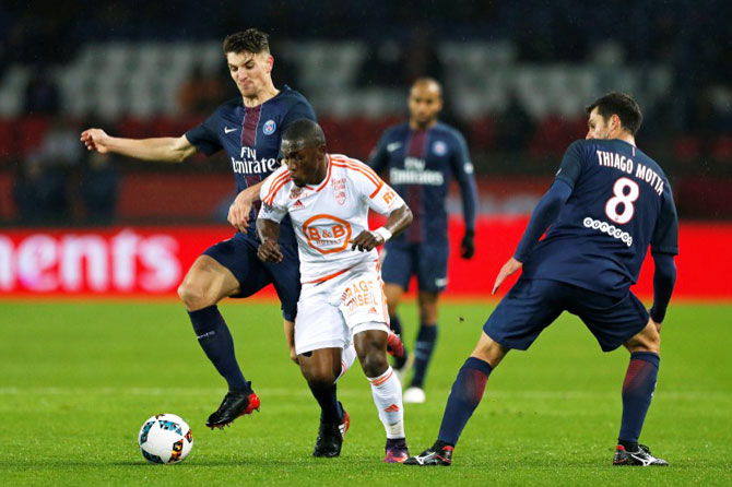 Paris St Germain's Thomas Meunier (left) is challenged by FC Lorient's Majeed Waris (centre)