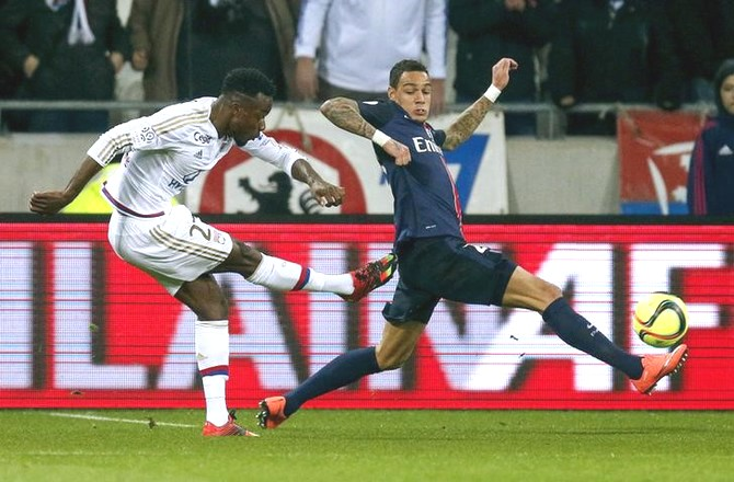 Olympique Lyon's Maxwel Cornet (left) shoots to score past Paris St-Germain's Gregory Van Der Wiel during their Ligue 1 match at the Grand Stade stadium, in Decines, France on Sunday