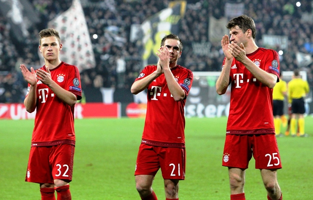 Joshua Kimmich, Philipp Lahm and Thomas Muller of FC Bayern Muenchen salute the fans