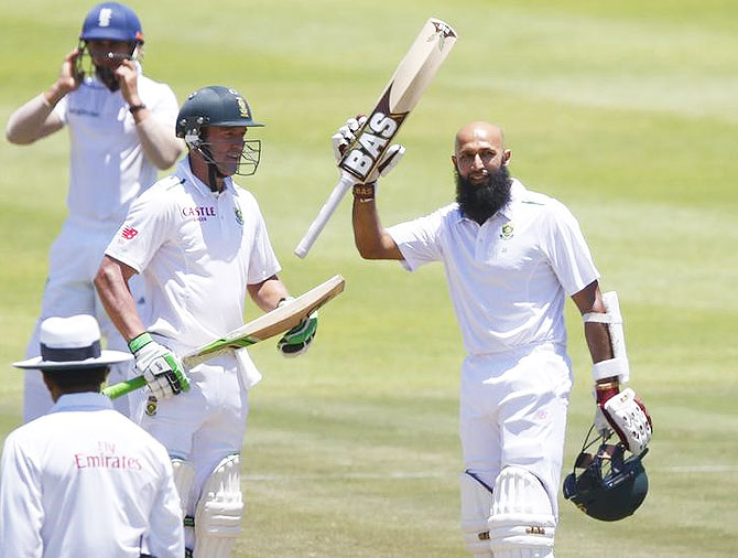 South Africa's Hashim Amla (right) celebrates scoring a century with AB de Villiers during the second cricket Test match against England in Cape Town on Monday