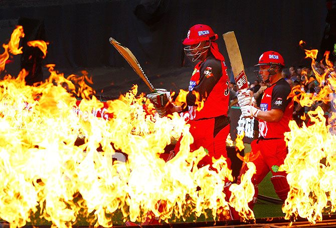 Chris Gayle and Aaron Finch of the Melbourne Renegades walk through flames to open the batting during their Big Bash League match against the Perth Scorchers at Etihad Stadium in Melbourne on December 30, 2015