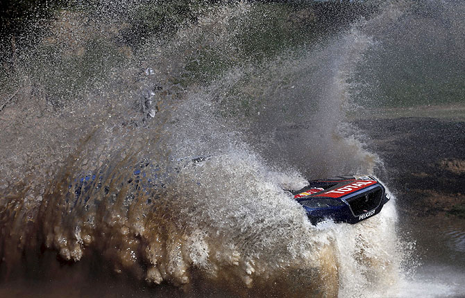Sebastien Loeb of France drives his Peugeot through the water during the Buenos Aires-Rosario prologue stage of Dakar Rally 2016 in Arrecifes, Argentina, on January 2, 2016