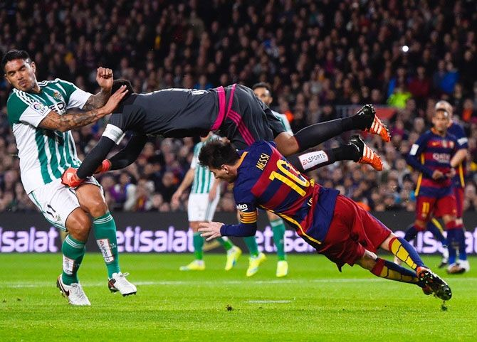 FC Barcelona's Lionel Messi and Real Betis's Adan, centre, clash during their La Liga match on Wednesday