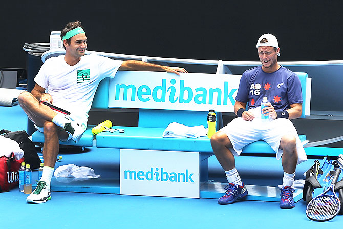 Switzerland's Roger Federer (left) talks with Australia's Lleyton Hewitt during a practice session at Melbourne Park on Friday