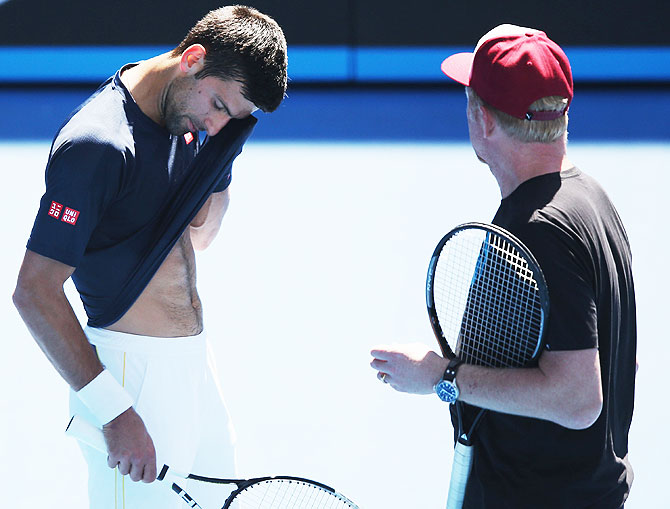 Novak Djokovic wipes away sweat as he talks with coach Boris Becker during a practice session
