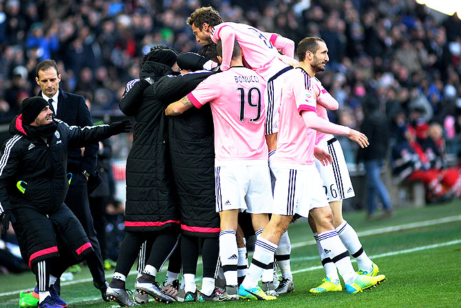 Juventus FC's Paulo Dybala is mobbed by teammates after scoring his team's opening goal against Udinese Calcio