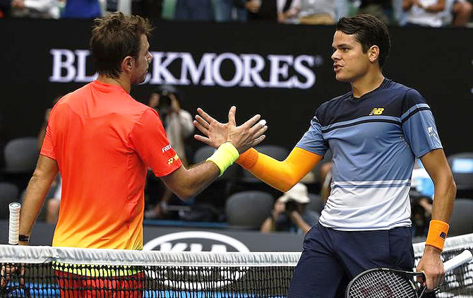 Milos Raonic (right) greets Stan Wawrinka at the net after winning their fourth round match