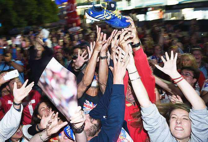 Serbian supporters wrestle for Novak Djokovic's shoe after he threw it into the crowd in garden square in Melbourne