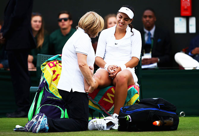 Croatia's Ana Konjuh receives treatment on her ankle during her second round match against Poland's Agnieszka Radawanska