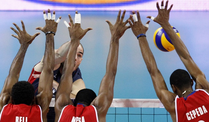 Clayton Stanley (rear) of the US spikes the ball against Yenry Bell, Isbel Mesa, centre, and Rolando Cepeda, right, of Cuba during their FIVB World League semi-finals men's volleyball match