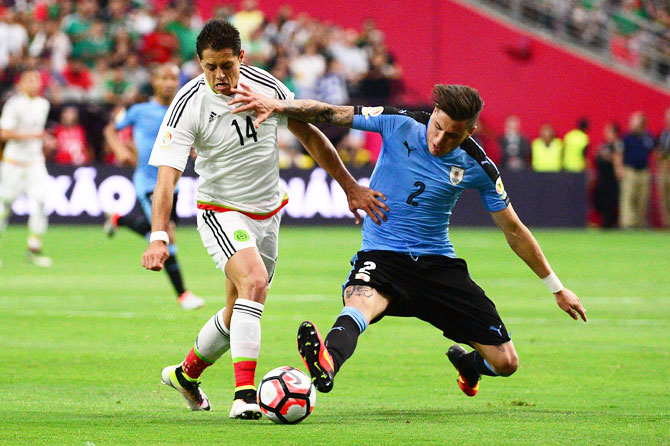 Mexico's Javier Hernandez (left) wins the ball during a challenge against Uruguay's Jose Gimenez