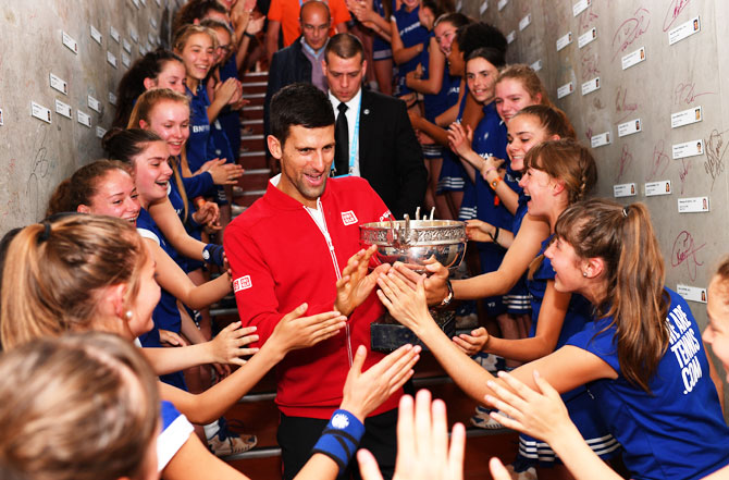 New French Open champion Novak Djokovic celebrates with the ball girls following his victory at Roland Garros on Sunday