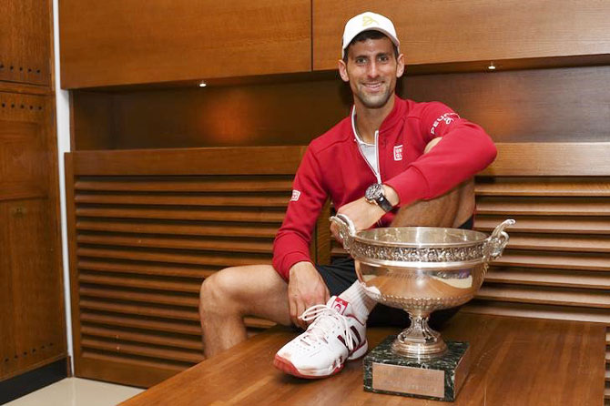 Novak Djokovic poses with trophy after winning the French Open on Sunday