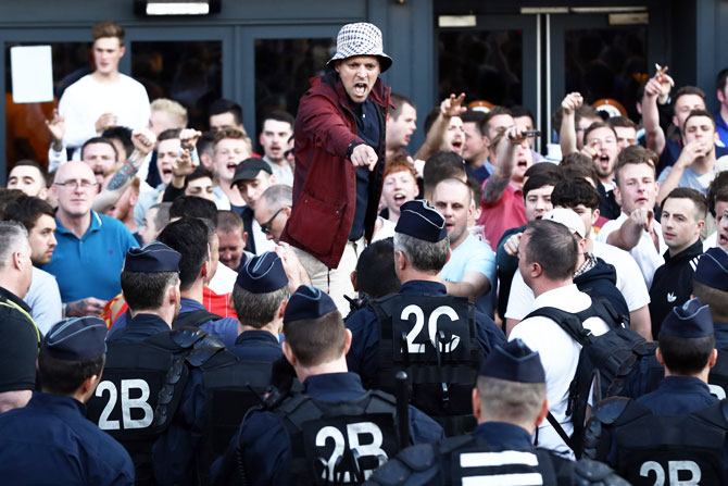 An English football fan gestures at police officers as supporters gather outside a pub in Lille on Wednesday
