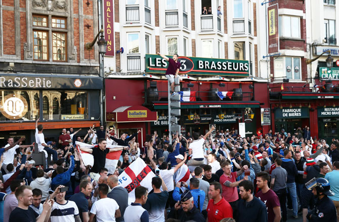 An England football fan climbs a road sign as supporters gather outside a pub in Lille on Wednesday