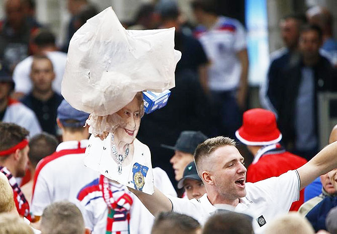 A garbage bag, thrown amongst fans, flies over a cutout of Britain's Queen Elizabeth II as fans celebrate their team's win over Wales in Lille