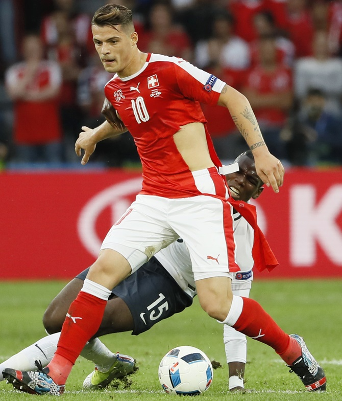 Switzerland's Granit Xhaka has his shirt ripped after a challenge by France's Paul Pogba during their Euro match