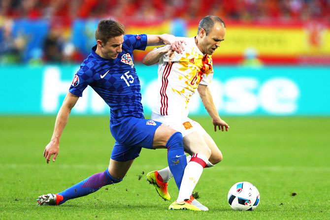 Spain's Andres Iniesta is challenged by Croatia's Marko Rog